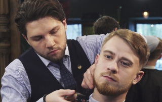 Professional barber grooming handsome young man